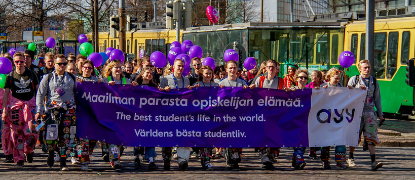 "Students walking with a banner ""The best students life in the world"""